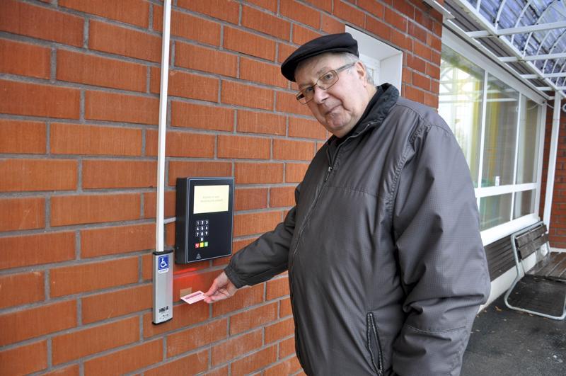 Kirjastokortilla sisään. Matti Uusi-Rauva pitää itsepalvelukirjastoa erinomaisena palveluna. Teippimerkki seinässä näyttää, millä korkeudella korttia on pidettävä, että lukija toimii.