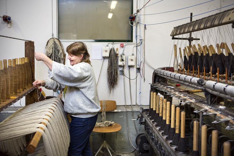 Nina Karkulahti työskentelee vyyhtikoneella merijärvisessä Kehräämö Christinassa. Yritystoiminta sai alkunsa Karkulahden innostuksesta käsitöihin.