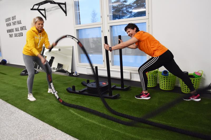 Yrittäjät Minna Huhmarniemi ja Katja Klemettilä esittelevät toiminnallisen treenin aluellta, jolla voi tehdä esimerkiksi köysijumppaa ja lykätä kelkkaa.