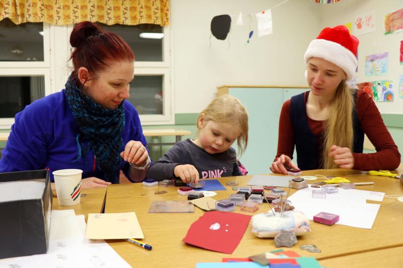 Kolmevuotias Ella Forsbacka (kesk.) keskittyi koristelemaan joulukortteja leimasimella 4H:n järjestämässä joulupajassa. Vieressä äiti Satu Forsbacka (vas.) ja 4H-yhdistyksen toiminnanohjaaja Emilia Känsälä.