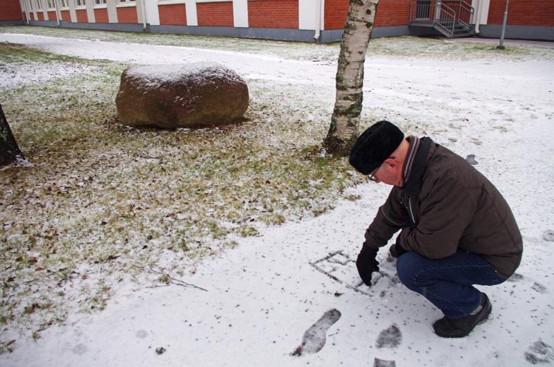 Juhani Kivijuuri piirtää lumeen Suojeluskunnan talon pohjaa ja perheensä asuntoa sinne.