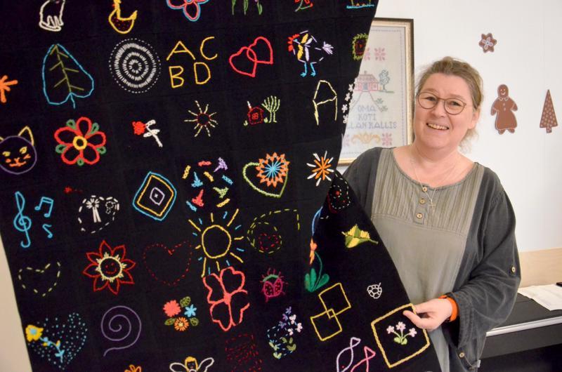 Seinävaaatteen tarinaa kertomassa kansalaisopiston tekstiilityönopettaja Sari Vierimaa.