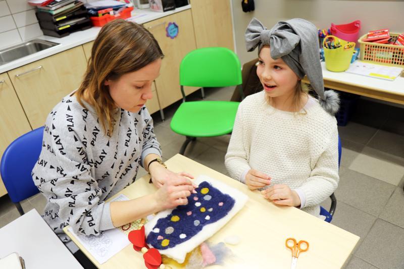 Lilli Kankkonen (oik.) opasti Mari-äidilleen neulahuovutusteknikkaa Taito-käsityökoulun syyskauden viimeisellä kokoontumiskerralla.