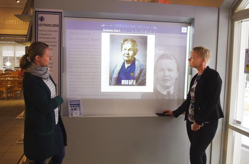 Museoamanuenssi Sini Näppä ja Lottamuseon johtaja Saija Ylitalo. Näytön kuvissa nivalalaislotta Katri Järviluoma.