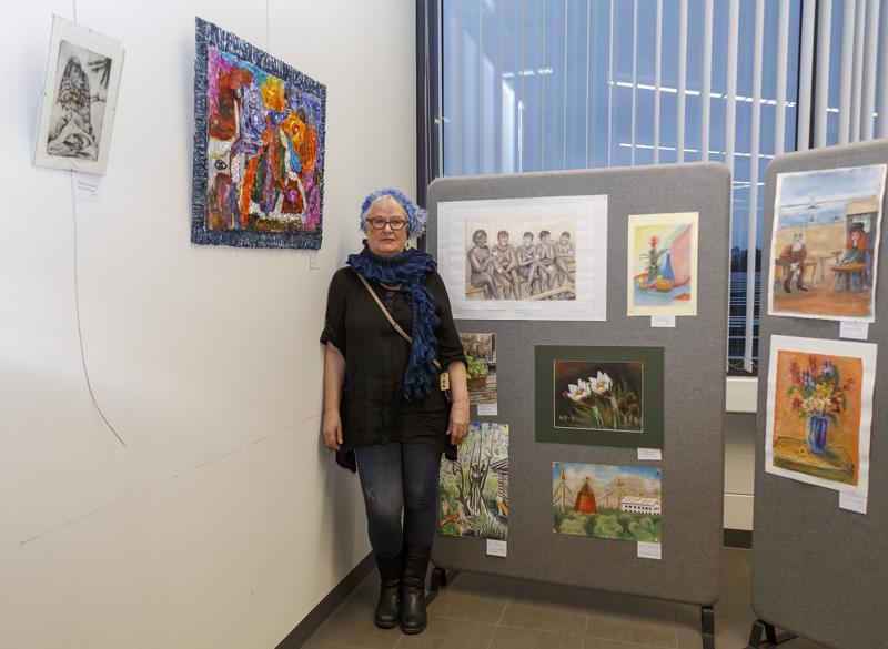 Maritta Lindberg värikkään Eksyksissä-kollaasiteoksensa luona, joka näkyy vasemmalla. Kuvassa on myös muiden jäsenten teoksia.