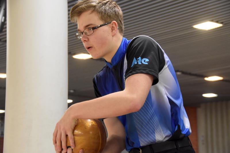 Simon Tissarinen heittää keilapalloa kahdella kädellä, kuten useimmat juniorit nykyisin.