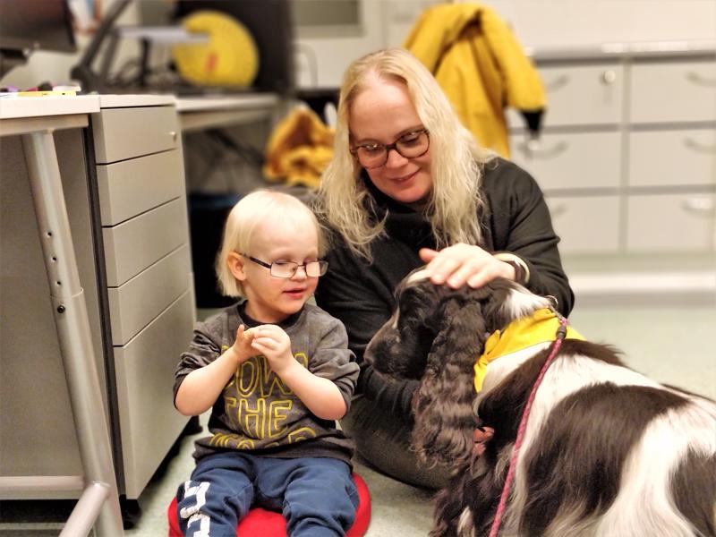 Erityisluokka Otavan opettaja Virve Tuominen-Suarez  silittää Merja-koiran päätä lukuhetken lopuksi. Valtteri ihastelee sen valloittavia luppakorvia....