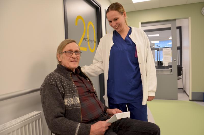 Sieviläinen Jari Suhonen odottelemassa lääkärille pääsyä, ennen sitä hän jututtaa vastaanottoapulaista, lähihoitaja Helianna Kähtävää.