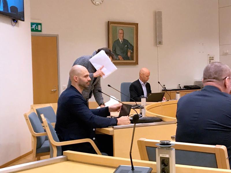 Käräjäoikeudessa on syytettynä törkeästä rahanpesusta neljä miestä. Kuvassa syytetty peittää kasvonsa, hänen vieressä on asianajaja ja taaempana syyttäjä.