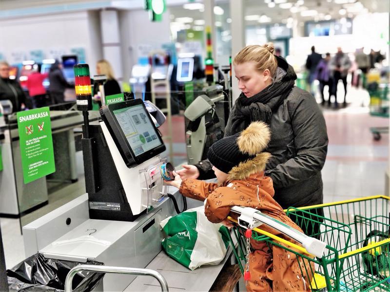 Karoliina Finnström Luodosta piippaa ostoksia Pietarsaaren Prisman uudella itsepalvelukassalla yhdessä Anton-pojan kanssa.  Itsepalvelualueelle on asennettu viisi itsepalvelukassaa, joista kaksi on isompaa hihnoineen ja pakkauspisteineen.