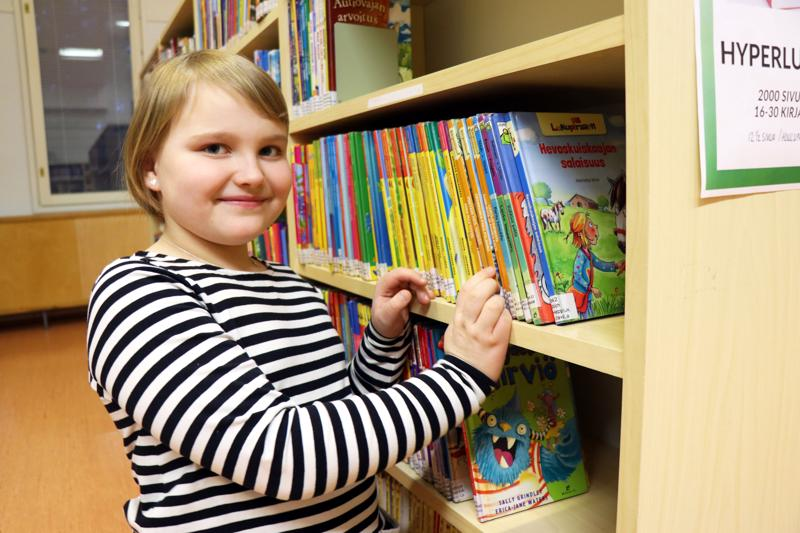 Jouluna lukemaan oppinut Enni käy ahkerasti lainaamassa luettavaa Rahkosen koulun yhteydessä sijaitsevasta kirjastosta.