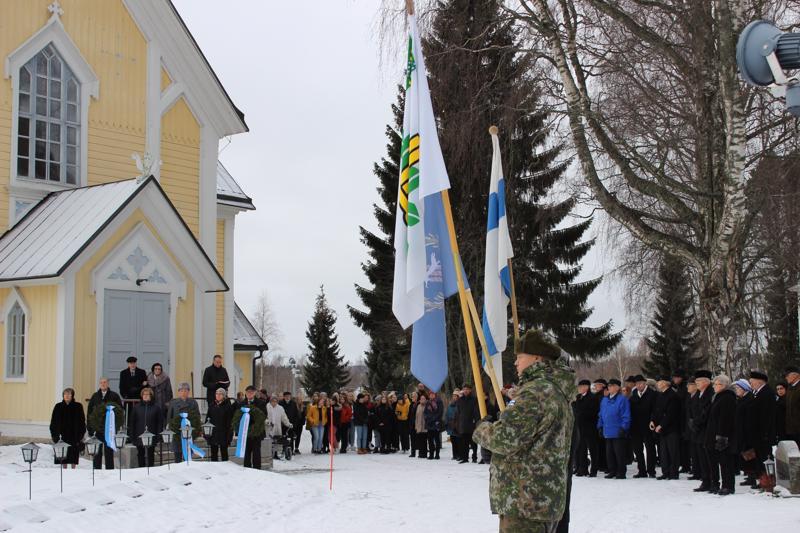 Tammisunnuntain lippukulkue pysähtyi kirkkomaalle seppeleen laskun ajaksi.