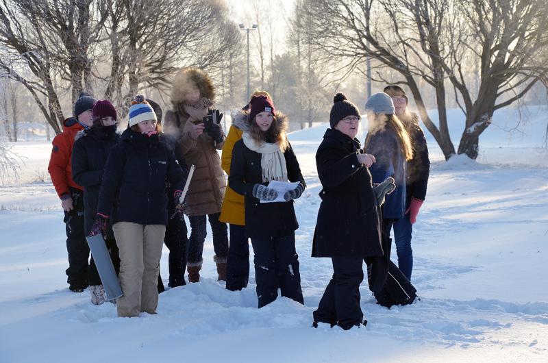 Erasmus-hankkeen koordinaattori Mervi Tikkanen opastamassa ylivieskalais-saksalais-espanjalais-kreikkalaista ryhmää tekemään lumitutkimusta kuplahallin viereisellä pellolla.
