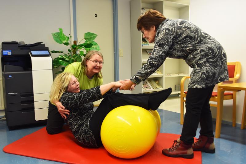 """Fysioterapeutti Arja Hälinen (kuvassa vasemmalla) sekä kurssilaiset Seija ja Aune näyttävät, kuinka lattialle kaatuneen ihmisen saa avustettua helposti ylös pallon avulla. Homma hoituisi yhdeltäkin avustajalta. """"Pähkinäpalloja"""" on jo Haapavedellä käytössä kotihoidossa ja asumispalveluissa."""
