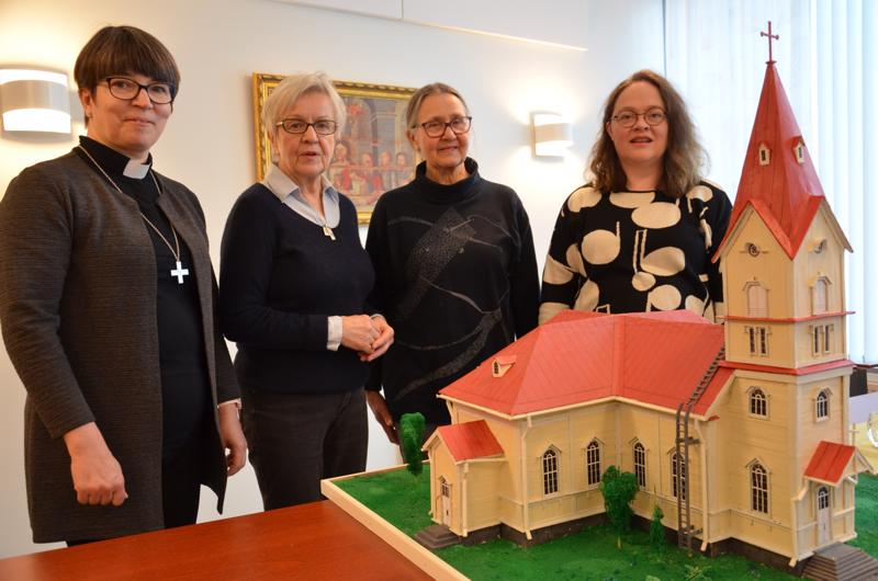 Eija Nivala, Kaija-Maija Perkkiö, Maija-Liisa Vuolteenaho ja Marita Kaakinen Ylivieskan palaneen kirkon pienoismallin äärellä. Kuorodraaman kahdella esityksellä tuetaan uuden kirkon rakentamista.