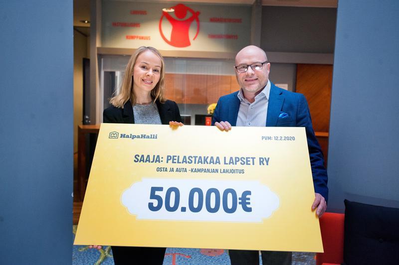 Yritystiimin vetäjä Heli Le otti Pelastakaa Lapset ry:n puolesta lahjoituksen vastaan HalpaHallin markkinointipäällikkö Juha Hakalalta.