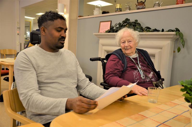 """Ylivieskalainen Temesgen """" Teemu"""" Abrhaley on ALVA-verkoston kautta ahkera vapaaehtoistyöntekijä. Hän  tykkää vapaa-ajallaan auttaa vanhuksia. Tässä hän lukee suomeksi Sipilän palvelukeskuksessa ja kuulolla vieressä on istumassa vanha tuttu Rauha Hannula."""