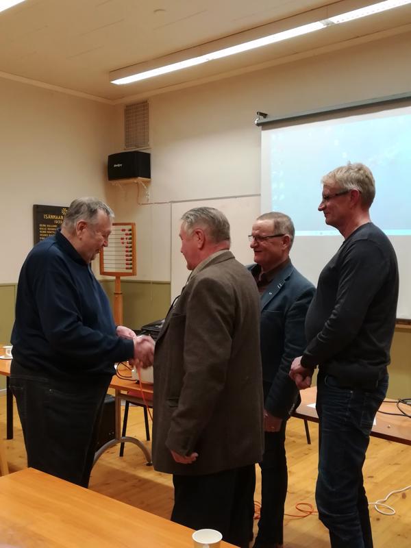 Armas Korkiakoski (vas.) vastaanottaa kultaisen ansiomerkin. Merkkiä luovuttamassa Harri Hepo-oja, Sakari Muuttola ja Juha Myllylahti.
