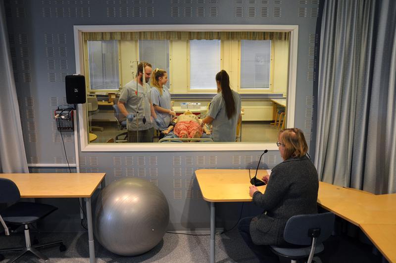 Opettaja Päivi Marttila seuraa lasiseinä läpi lähihoitajaopiskelijoiden työskentelyä simulaattoritilassa. Kaiuttimien kautta opettaja kuuleem, mitä opiskelijat keskustelevat ja itse hän voi antaa mikin kautta ohjeita.
