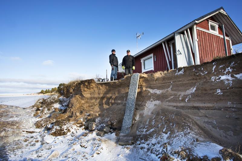 Mauri Sippola ja Osmo Heusala kertovat, että hiekkaa on alettava siirtämään rantaan heti, kun sää sen sallii. Heusalan mökin ja meren välillä ei ole enää kuin pieni pätkä hiekkaa, jonka myrskyaallot on leikannut pystysuoraan. Pudotus on yli pari metriä.