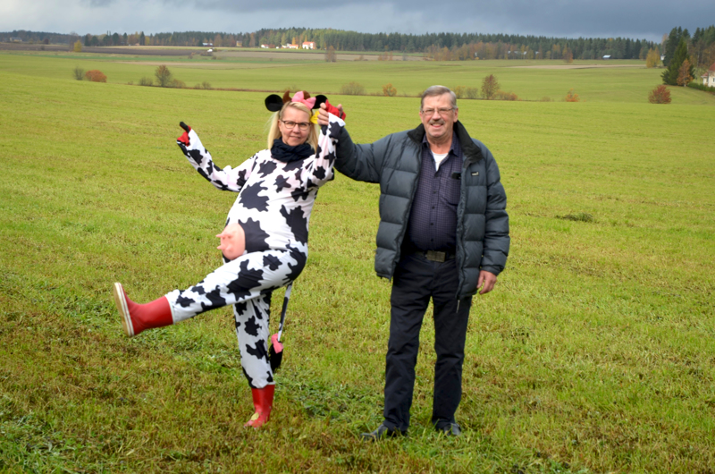 Silmille nautittavaa. Toholammin asuntotoimen markkinointiesitteen kannessa on kuva, jossa jokivarren maisemassa poseeraavat lehmäksi pukeutunut Maija Hjelmeroos ja kotiinpaluun tehnyt lännen mies, Sakari Kerola.