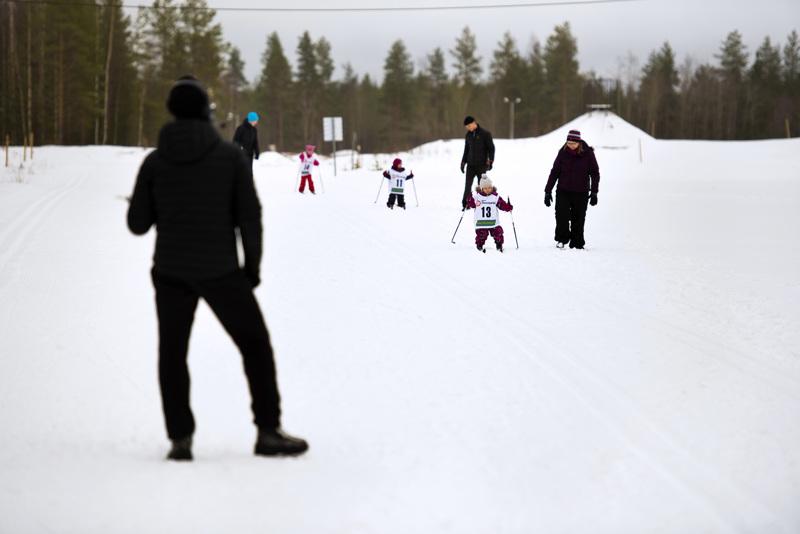 Huoltajat avustivat pienimpiä hiihtäjiä. Hiihtotapa oli vapaa, mutta moni valitsi silti perinteisen tyylin.