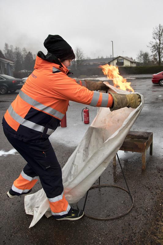 Marke Paavola ohjeistaa lähestymään palavaa kohdetta rohkeasti sammutuspeitteen kanssa. Ei riitä, että peitto heitetään kohteen päälle, vaan se on tukahdutettava kunnolla.