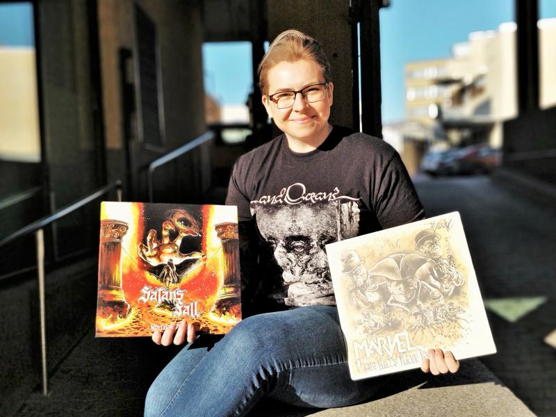 Anu Bring kädessään oma lemppari levynkansi Satans Fall -bändille sekä kahvilla maalattu levynkansi Märvel -bändille.