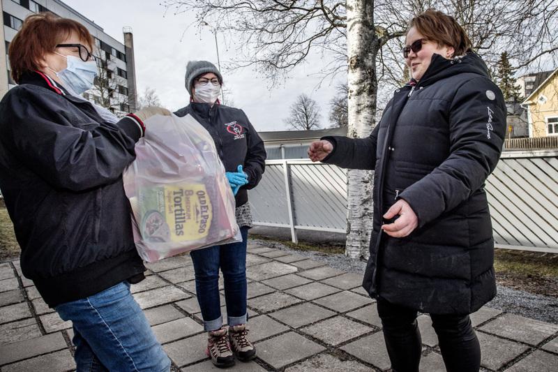 Aino Lindqvist ja Riitta Rekilä ovat ruuanjakeluvuorossa, pussin saa Tanja Anttila.
