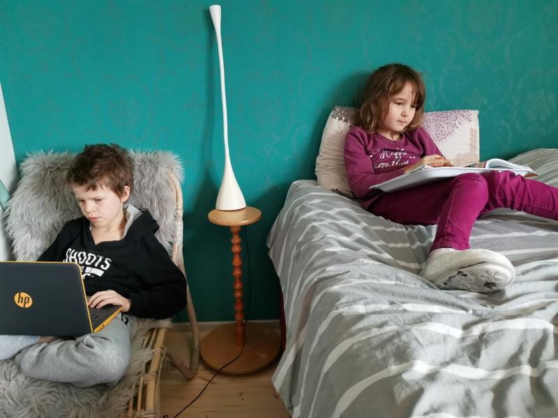 Koukan koti muuttuu päivisin pieneksi kouluksi, kun kuusi peruskoululaista tekee omia tehtäviään etäopetuksessa. Kuvassa Huuko tekee tehtäviä chromebookilla ja Jania sängyllä matikkaa.