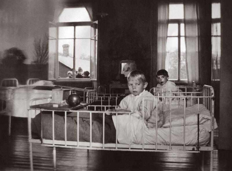 Lapsipotilaita kulkutautisairaalassa. Vasemman ikkunan takaa näkyy potilaiden omaisia.