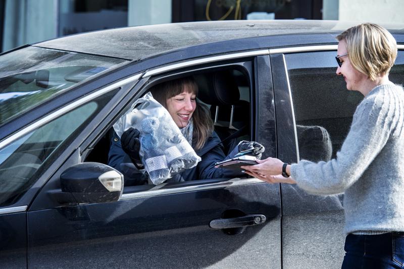 Sari Aho kiidättää lankapussin Katja Kentalalle autoon. Poikkeusoloissa on syntynyt uudenlaisia palvelumuotoja.