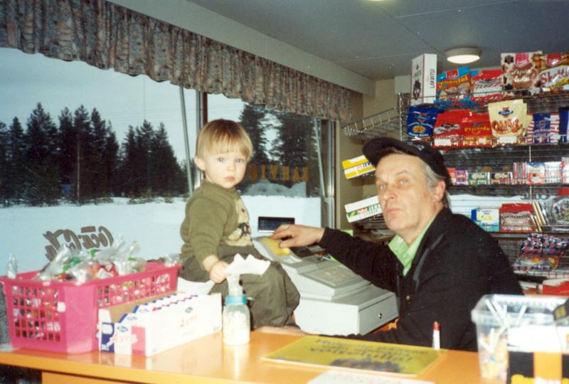 Pekka puuhamaassaan. Pekka Kauppinen kasvoi korjaamon ja huoltoaseman tunnelmassa. Vuonna 1977 Leena ja Pekka Kauppinen aloittivat yrittäjinä. Samalla yrityksen paikka Lestijärven kirkonkylän keskustasta siirtyi Halsuantien alkupäähän Kangasvieren risteykseen. Kuvassa Pekka ja Santeri, tyttären poika, valmiina palvelemaan asiakkata.