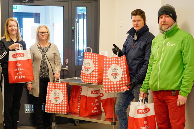 Halsualla yllätettiin perheet perjantaina hedelmäkasseilla, joka piti sisällään 30 euron ostokortin oppilasta kohden. Kuvassa erityisopettaja ja tuleva rehtori-sivistysjohtaja Hanne Jylhä, toimistosihteeri Mervi Patana, taksiautoilija Antti Alanko sekä Vastepiste-hankkeen Janne Känsäkoski.