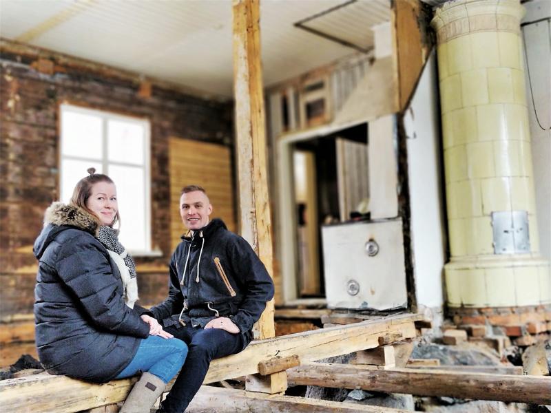 Marjo ja Jarkko Vuorinen tulevassa tupakeittiössä, jossa luovat tunnelmaa paljaat hirsiseinät, kaakeliuuni ja puuhella.