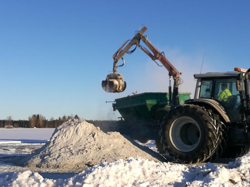 Kevättalvi on peltojen kalkitusaikaa. Mika Hautajoki nostaa kalkkia kuormaimella levitysvaunuun.