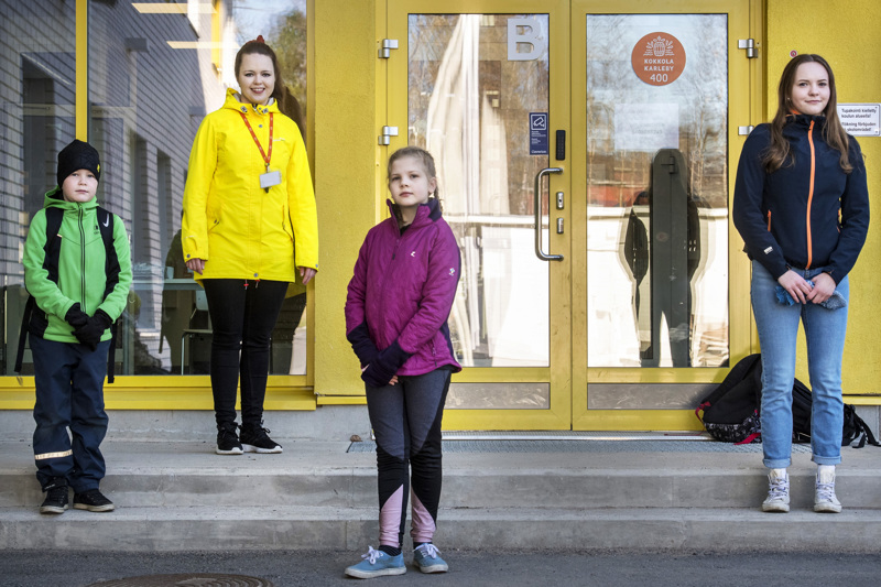 Reko Kuutsa, Amanda Ylitalo ja Iitu Riippa Torkinmäen koulun pääovella ennen ovien aukaisemista. Takana keltaisessa takissaan luokanopettaja Minnamari Mäkelä.
