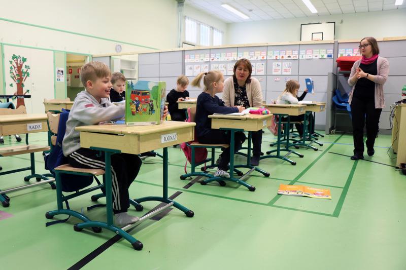 Oksakosken koulun väki on tällä hetkellä väistössä koulun liikuntasalissa, joka on jaettu sermeillä luokkatiloiksi. Kuvassa koulun vararehtori Katja Hytösen (oik.) opettama eka- ja tokaluokkalaisten ryhmä.