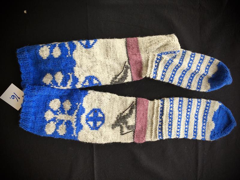 16. Halusin että sukissa on vaakunaa, helmillä koristelin suksen sompan kultaiset nastat. Hiihtäjäpatsas seisoo sukassa ja väritys kuvastaa vettä. Katja Dahlman. TUOMARIT: Hyvin tiivistetty Haapavettä kuvaavat elementit.