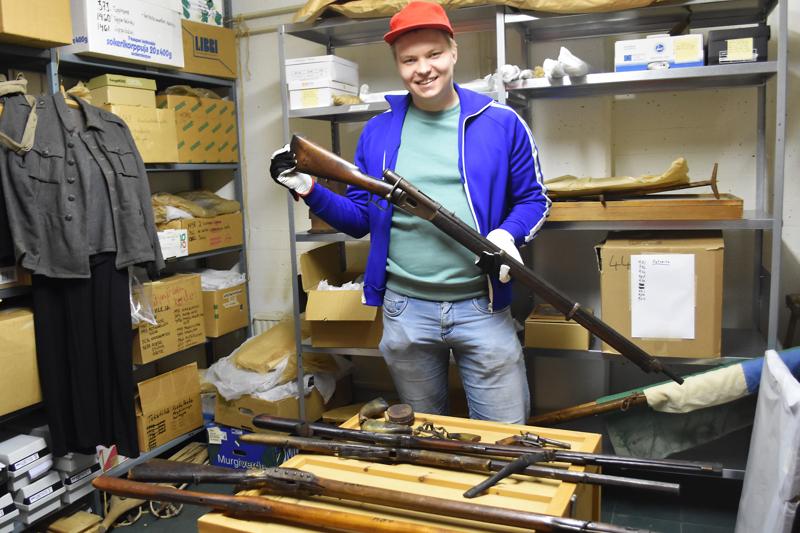 Museonhoitaja Juha Huttula esittelee asekokelmiin kuuluvaa Grafton-kivääriä.
