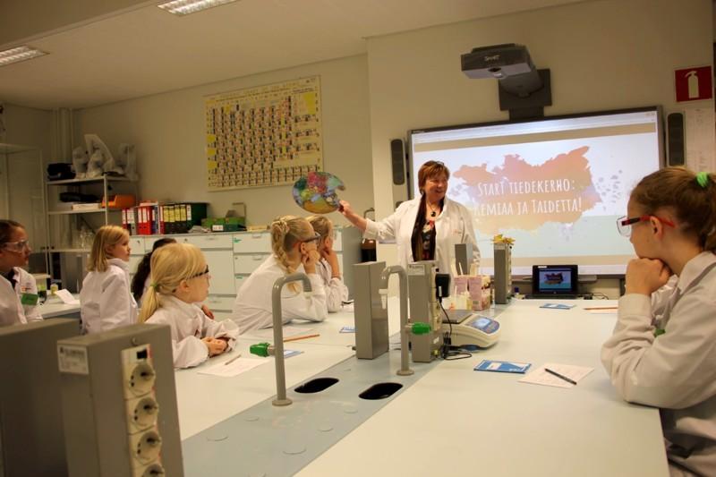 Itsekin maalaamista harrastava professori Maija Aksela opastaa lapsia luonnontieteiden ja taiteen yhdistämiseen lasten tiedekerhossa. Luonnontieteitä ja taiteita yhdessä!