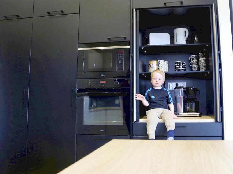 Aamiaiskaappi piilottaa kahvinkeittimen, leivänpaahtimen ja muut pienet keittiökoneet. Kaappiin mahtuu myös lapsi, kuten Reino kuvassa esittelee.