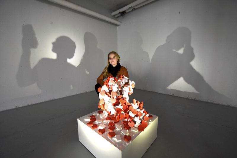 Anni Laukan teoksessa sosiaalisesta mediasta tutut peukut ja sydämet muodostavat veistoksen, joka heittää kaksi erilaista varjoa seinille.