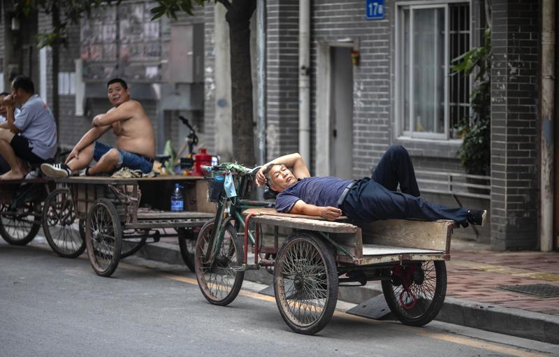 Pyöräkuljettajat olivat päivälevolla toukokuun puolivälissä Guangzhoussa. Kiinassa on pandemian vuoksi jäänyt työttömäksi kymmeniä miljoonia ihmisiä.