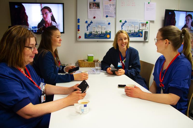 Vaasan keskussairaalan työntekijät Tarja Makkonen (vasemmalla), Ann-Marie Knip, Niina Rintamäki ja Mari Franssila ovat mukana kolme viikkoa kestävässä Ketju-sovelluksen testissä. Esimerkiksi kahvitauolla ahtaissa tiloissa ei voi välttyä lähikontaktilta.