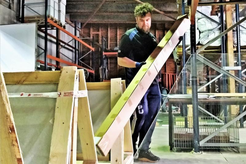 Pauli Saarikettu työn touhussa Kivikankaan varastolla. Kasvihuoneet toimitetaan paketissa; rungot ja lasit omissaan.  Laseille rakennetaan ennen matkaan lähettämistä omat kuljetuslaatikot puusta.  Kasvihuoneiden maahantuojana Kivikangas on Suomen vanhin.