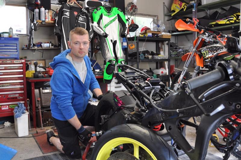 Miika Viiperi vaihtaa moottoripyörään rengasta isänsä autotallissa.