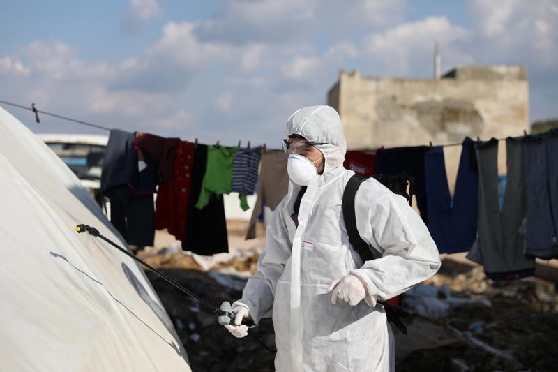 Koronavirus voi lisätä halua paeta pakolaisleiriltä. Vapaaehtoinen ruiskuttaa desinfiointiainetta varotoimenpiteenä koronavirusta vastaan leirillä lähellä Syyrian Idlibin kaupunkia.