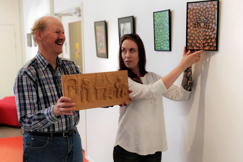 Bo Lillqvistillä on kädessään puusta veistetty kohokuva tupainteriööristä aikojen takaa, Camilla Fagerholmilla yksi mandalan innoittamista tussipiirroksista.