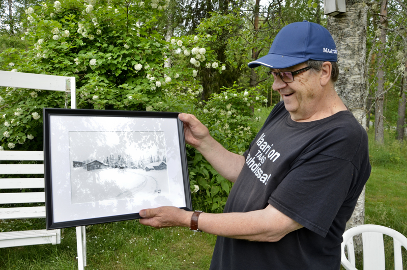 Juhani Alaranta esittelee yhtä Vanhasen tauluista. Tauluissa on talvisia maisemia.